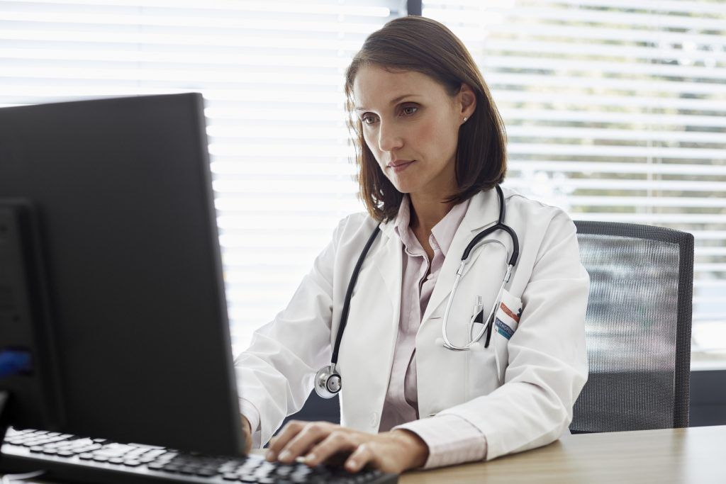 female-doctor-wearing-lab-coat-and-stethoscope-sitting-at-desk-working-on-sensitive-information-at-computer-monitor