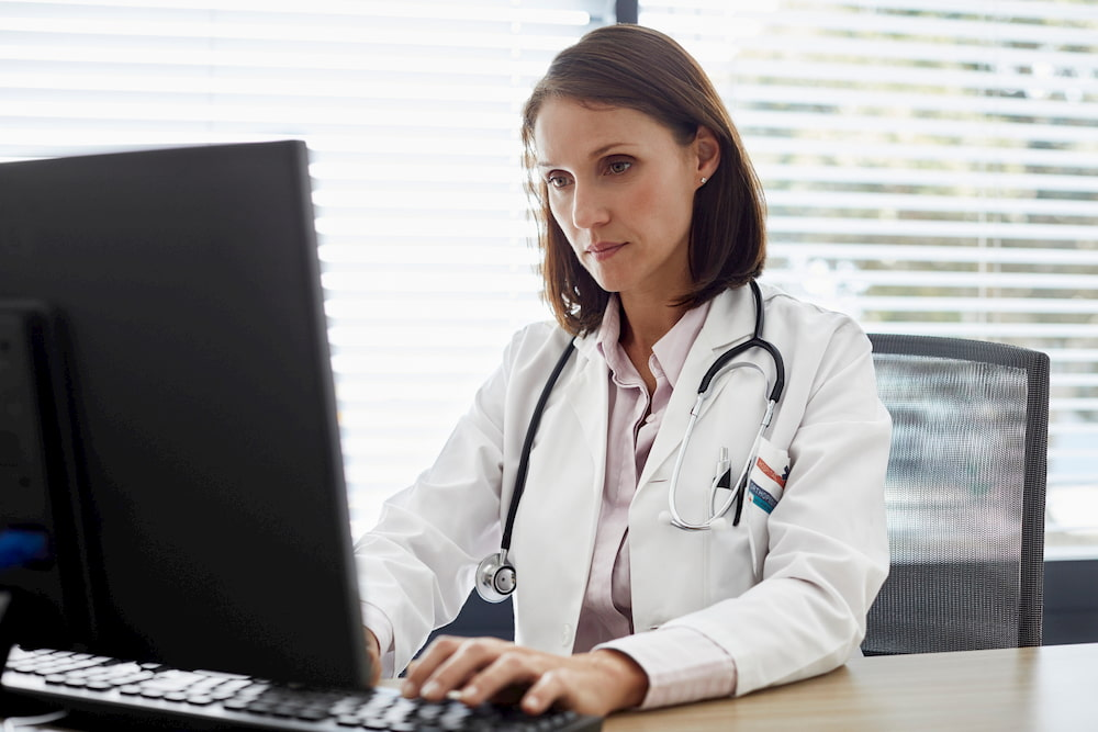 Confident doctor working on computer at desk. Female health professional is working in office.