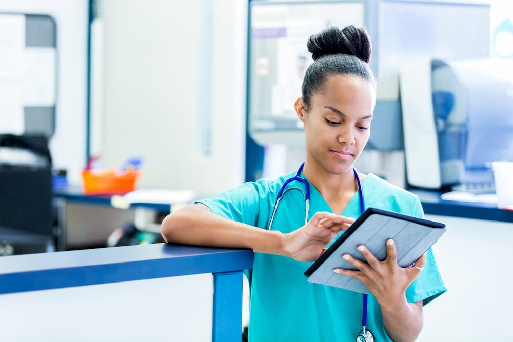 Nurse updating digital patient charts in modern emergency room.
