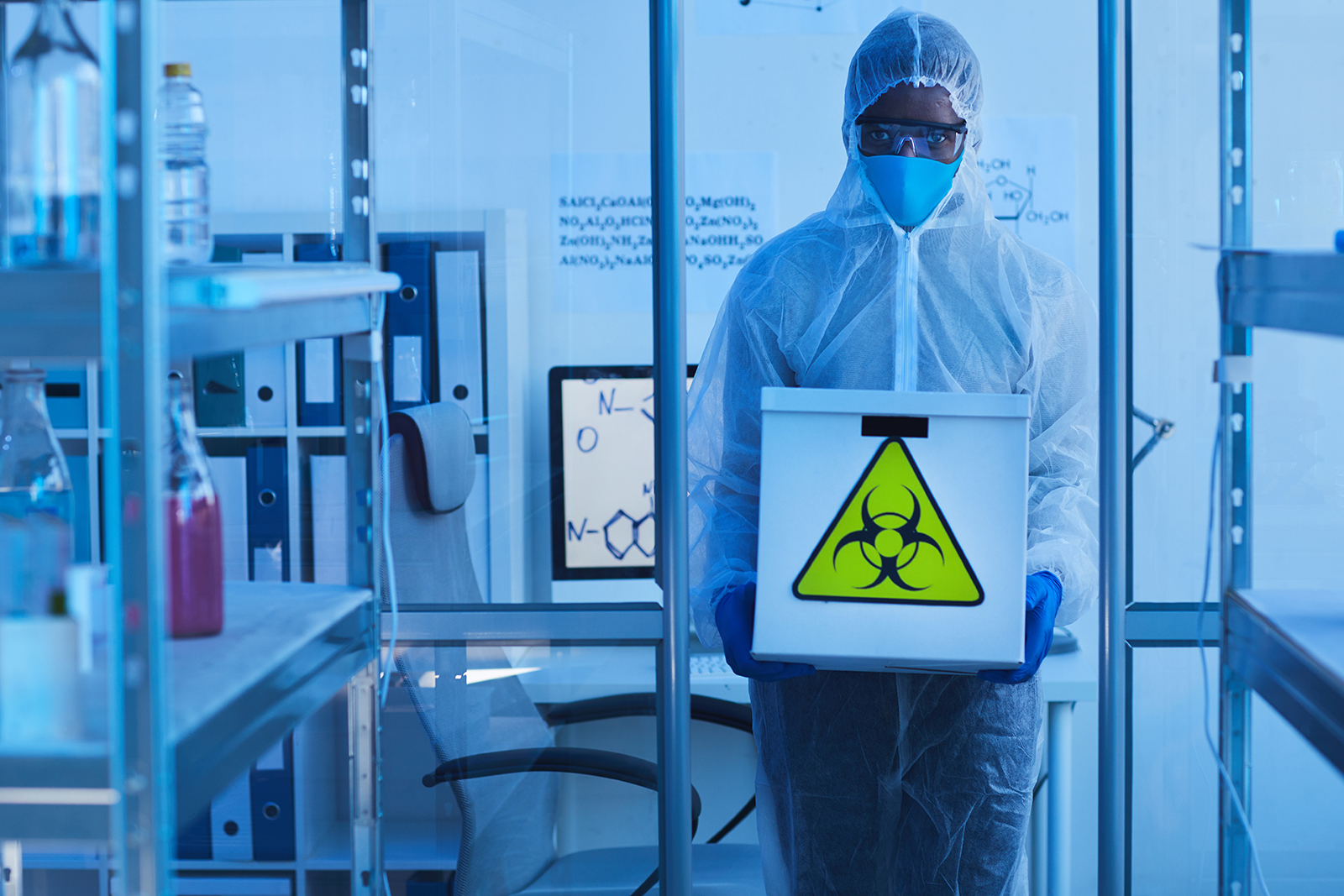 Horizontal medium long shot unrecognizable male laboratory worker in modern protective suit holding box with biological hazards
