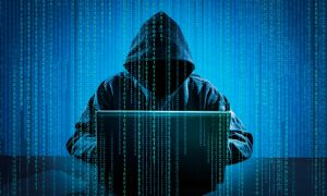 A hacker in a black hoodie sits at a laptop amid columns of numeric code, illustrating the need to store passwords safely.