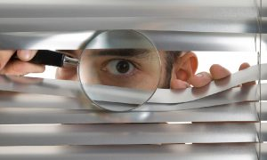 A man uses a magnifying glass to peer through window blinds, illustrating the lack of online privacy.