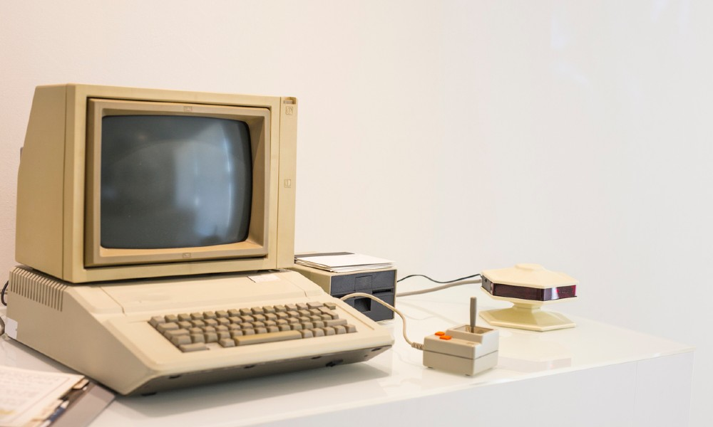 Vintage Macintosh computer that comes equipped with a hard disk drive, joystick, monitor, and keyboard