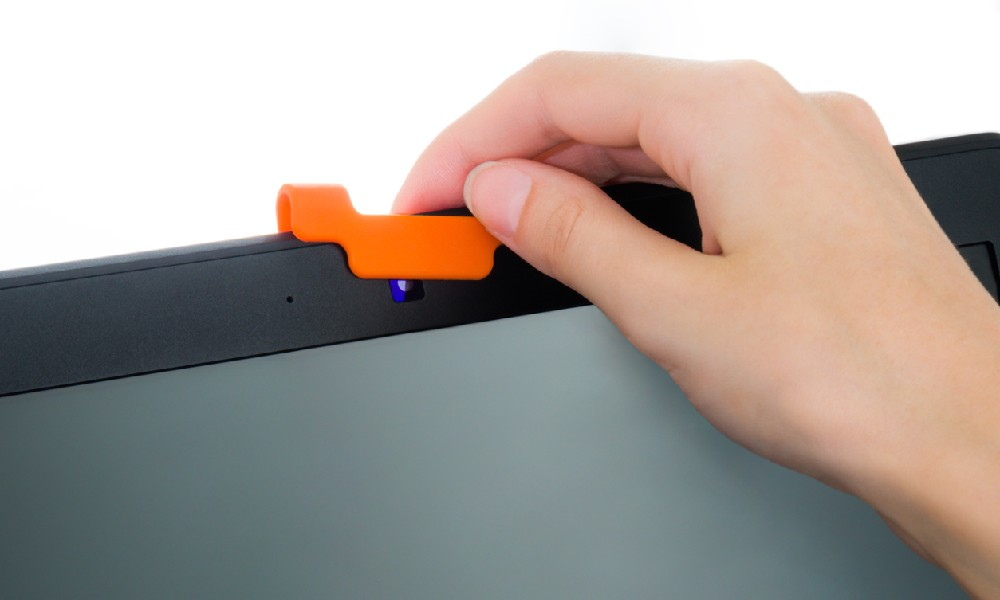 Hand protecting a computer webcam with an orange cover, which would be an excellent cybersecurity gift