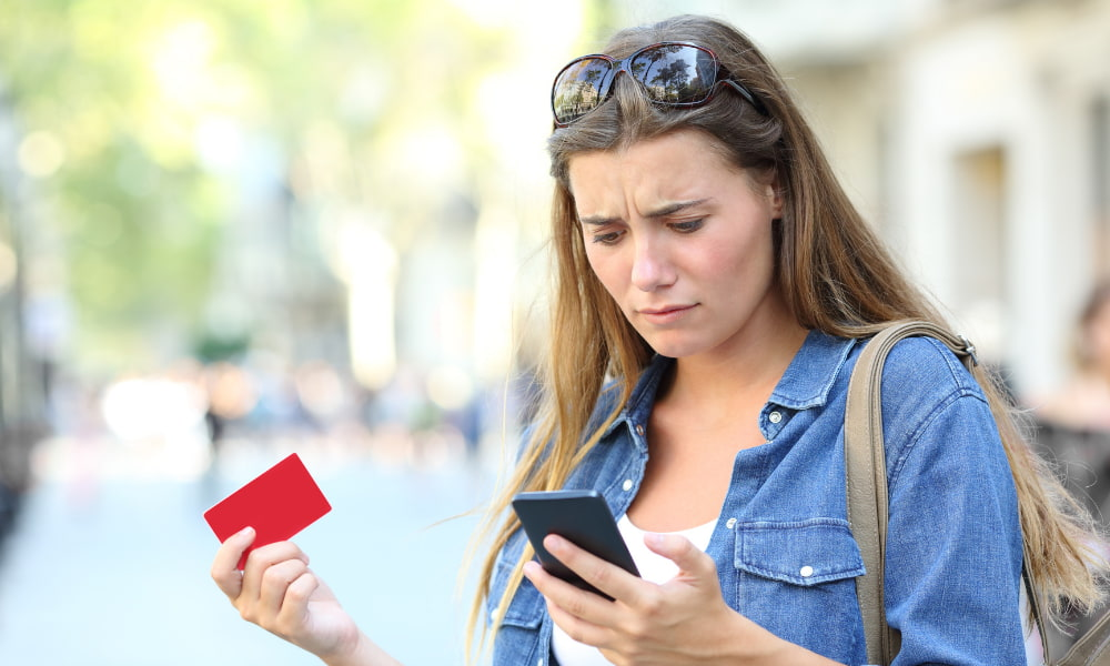 Person looking at card typing it into a phone