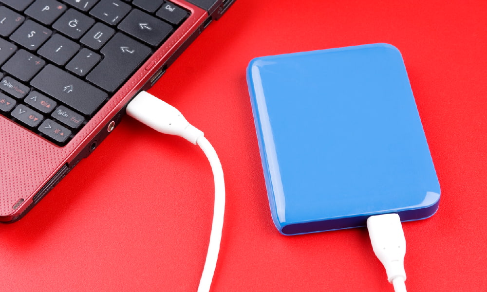 A blue external hard drive plugged into a red laptop computer, with both the drive and computer on top of a red table, illustrating how to partition external hard drives.