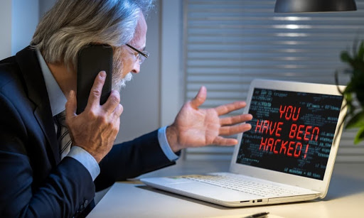 A man on the phone during a vishing attack gets a message on his computer that it's been hacked.