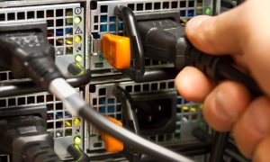 A person's hand plugs a power cable into the PC power supply in the back of a computer.