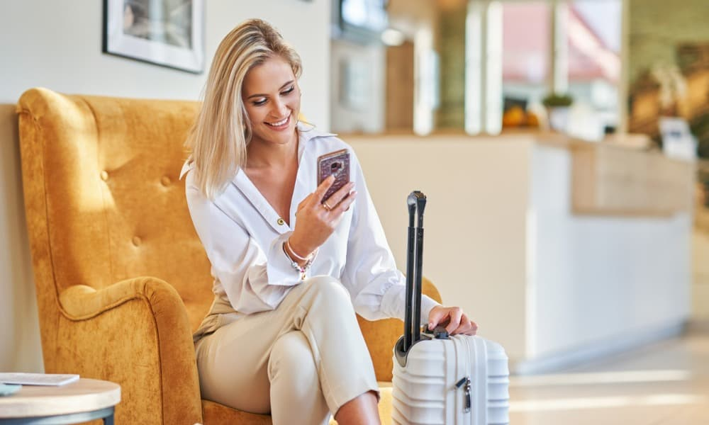 woman sitting in hotel lobby using VBN on her smartphone with luggage next to her