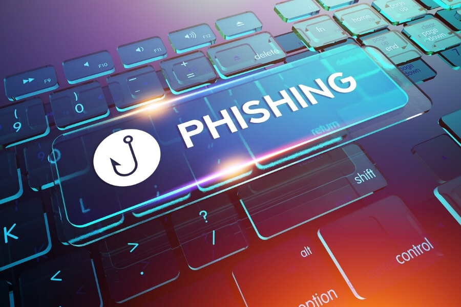 Key displaying the word phishing in front of a keyboard showing a phishing attack in progress