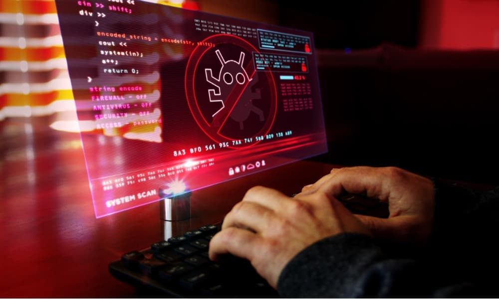 A man typing on a computer that has been infected by a virus or a worm.